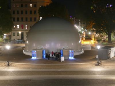 Mobile, inflatable infinityDome in exterior view at night as venue for an extraordinary art event.
